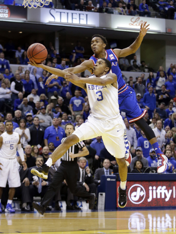 Kentucky's Tyler Ulis (3) puts up a shot against Kansas's Devonte Graham during the second half of an NCAA college basketball game Tuesday, Nov. 18, 2014, in Indianapolis. Kentucky won 72-40. (AP  ...