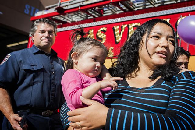 Las Vegas firefighter Ben Kole, left, Yadira Gonzales and her daughter Alexa, 14 months, attend a ceremony at Las Vegas Fire Station No. 108, 4555 E. Bonanza Road, on Wednesday, Nov. 5, 2014. Kole ...