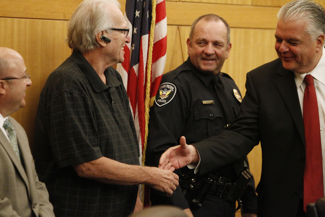 Dano McKay, left, shakes hands with Clark County Commissioner Steve Sisolak, right, as Robert Gibbs watches during a presentation to honor Gibbs at the Clark County Government Center in Las Vegas  ...