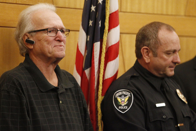 Dano McKay, left, stands with Robert Gibbs during a presentation to honor Gibbs at the Clark County Government Center in Las Vegas Tuesday, Nov. 18, 2014. Gibbs, a retired Las Vegas police officer ...