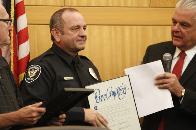 Robert Gibbs, center, is presented with a proclamation by Clark County Commissioner Steve Sisolak, right, during a presentation to honor Gibbs at the Clark County Government Center in Las Vegas Tu ...