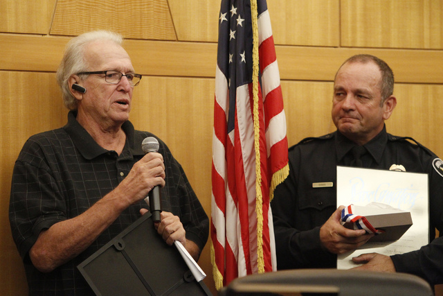 Dano McKay, left, speaks during a presentation to honor Robert Gibbs, right, at the Clark County Government Center in Las Vegas Tuesday, Nov. 18, 2014. Gibbs, a retired Las Vegas police officer, w ...