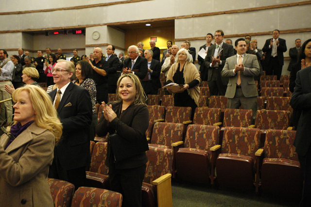 People stand to recognize Robert Gibbs, a retired Las Vegas police officer, during a presentation at the Clark County Government Center in Las Vegas Tuesday, Nov. 18, 2014. Gibbs was honored for i ...