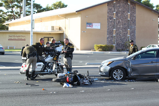Las Vegas police investigate an accident where a motorcyclist was hospitalized after colliding with another vehicle near Nellis Boulevard and Harmon Avenue, Wednesday, Nov. 19, 2014. (Chase Steven ...