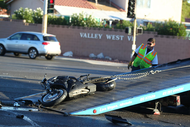 A motorcycle is loaded onto a tow truck as Las Vegas police respond to a three-vehicle crash, on Flamingo Road near Lindell Road, which involved the motorcycle whose driver fled the scene in Las V ...