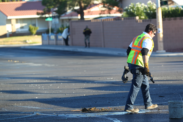 A tow truck operator cleans up debris as Las Vegas police respond to a three-vehicle crash at Flamingo and Lindell roads, which involved a motorcycle whose driver fled the scene and two other vehi ...