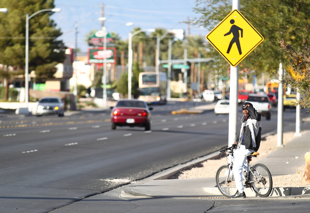 A man observes the scene as Las Vegas police respond to a crash involving a moped and a car near Harmon Avenue and Pancho Villa Drive, near Nellis Boulevard, in Las Vegas on Wednesday, Nov. 19, 20 ...