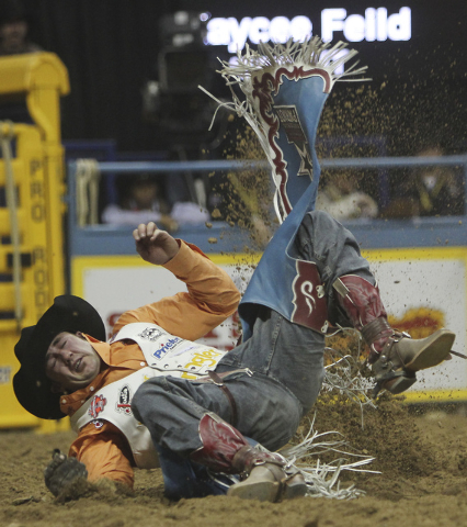 Kaycee Feild hits the ground hard during round 7 of the Wrangler National Finals Rodeo at the Thomas & Mack Center in Las Vegas on Dec. 12, 2012. (Jason Bean/Las Vegas Review-Journal)