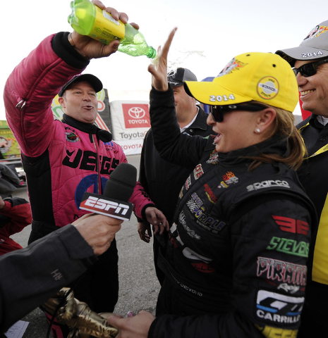 NHRA Pro Stock driver Jeg Coughlin, left, pours soda onto fellow driver and race winner Erica Enders-Stevens after Enders-Stevens defeated Coughlin in the final round of the Toyota Nationals at Th ...