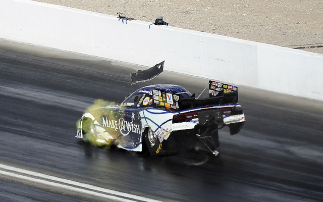 The burst panel on the NHRA Funny Car driven by Tommy Johnson Jr. flies off as he races alongside Matt Hagan in the second round of eliminations during the Toyota Nationals at The Strip at Las Veg ...