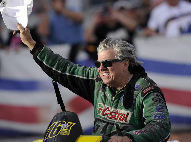 NHRA Funny Car driver John Force waves to the crowd after making a pass in the third round of eliminations during the Toyota Nationals at The Strip at Las Vegas Motor Speedway in Las Vegas Sunday, ...