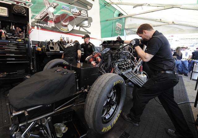 Crew members for NHRA Funny Car driver John Force prepare the car for the final round of eliminations of the Toyota Nationals at The Strip at Las Vegas Motor Speedway in Las Vegas Sunday, November ...