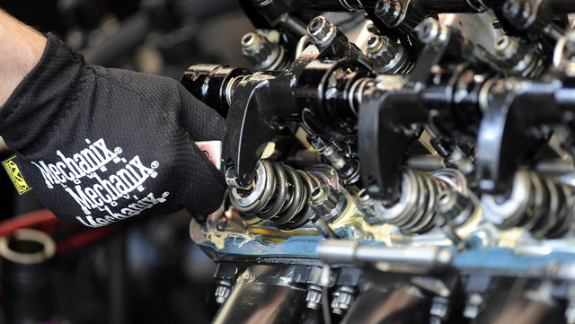 Crew member for NHRA Funny Car driver John Force uses a feeler gauge to check the clearance between the valve spring and valve seat prior to start of the final round of eliminations during the Toy ...