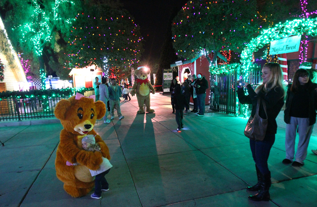 Devin Frey, right, takes a picture of her daughter, 2-year-old Stella, with Honey Bear at the Magical Forest at Opportunity Village in Las Vegas. (Chase Stevens/Las Vegas Review-Journal)