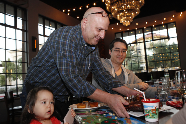 Food server Paul Grogan, center, delivers food to customers John Powell, right, and his daughter Zoey, 1, during dinner service at Pot Liquor C.A.S. at Town Square in Las Vegas Saturday, Nov. 15,  ...