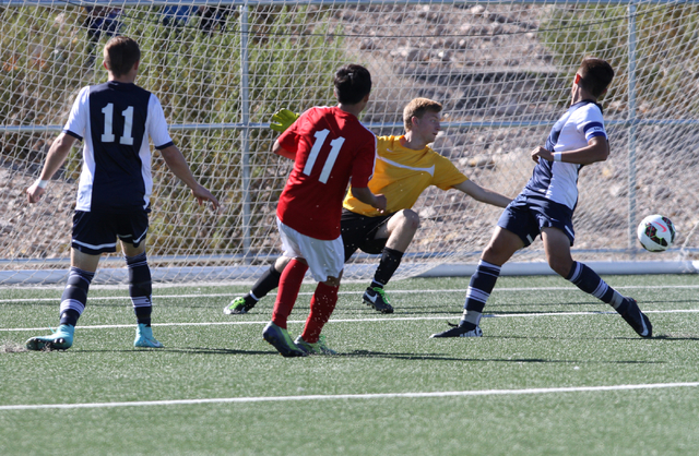 Valley's Marco Gonzales (11) makes goal after Foothills goalie Derek Lawson (00) unsuccessfully tries to block the ball, during the  2014 NIAA Division I Sunrise Region Boys Soccer Finals match, a ...