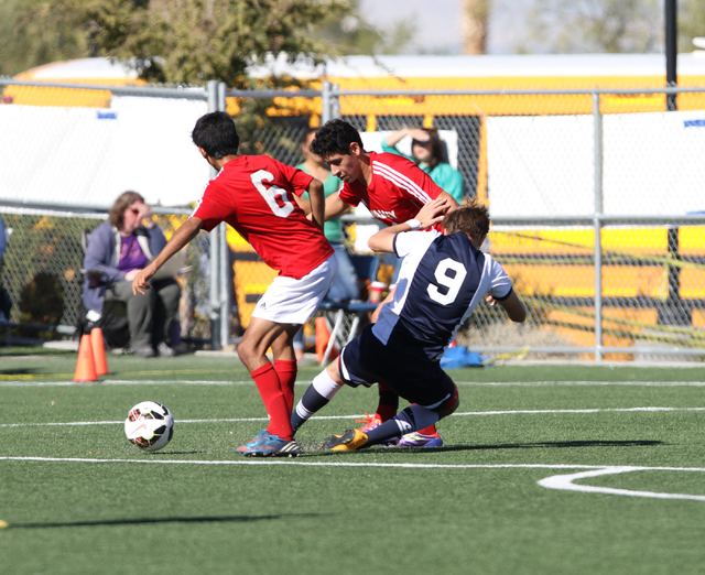 Valley's Juan Velazquez (6) and Valley's Alejandro Parra (9) collide with Foothillճ Jackson Dietrich (9) during the  2014 NIAA Division I Sunrise Region Boys Soccer Finals match, at Heritage ...