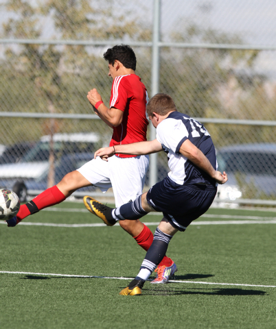 Foothillճ Michael Carnahan (10) kicks the ball while Valley's Luis Meza (4) stretches out to block the kick, during the  2014 NIAA Division I Sunrise Region Boys Soccer Finals match, at Heri ...