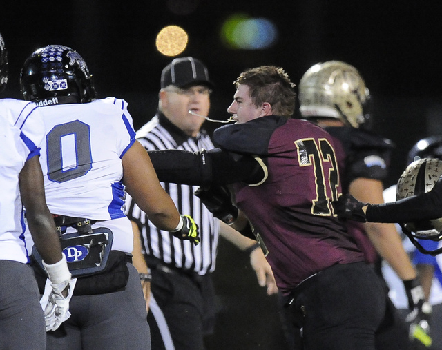 Faith Lutheran defensive lineman John Molchon (72) looses his helmet while guarding Desert Pines linebacker Traemaine Sevea (50) in the first half of their Division 1A Southern Region semifinal pr ...