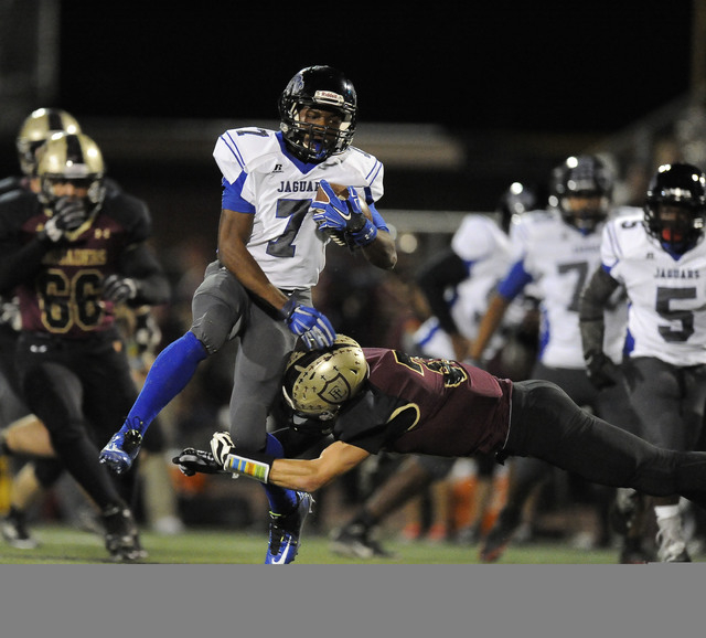 Desert Pines running back Isaiah Morris (7) eludes the tackle of Faith Lutheran defensive back Tyler Mahan (31) in the first half of their Division 1A Southern Region semifinal prep football game  ...