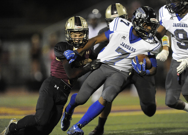 Desert Pines running back Isaiah Morris (7) is tackled by Faith Lutheran defensive back Robby Schwartz (3) in a Division I-A state quarterfinal. The Jaguars play Bishop Gorman in the state final a ...