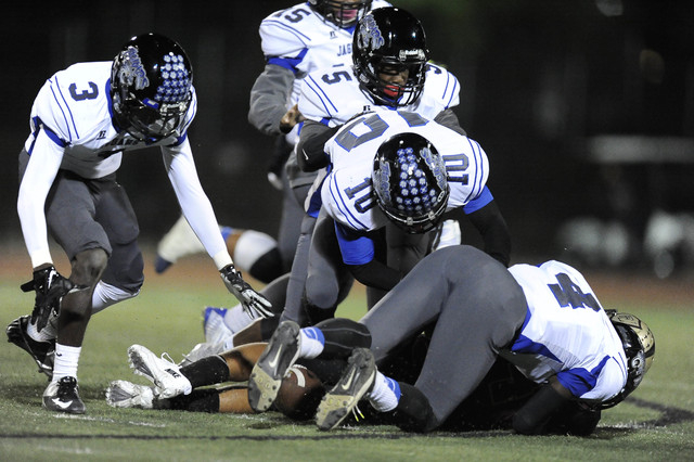 Desert Pines players Gianni Breland (3), Dillard Davis (5), and Jon McCoy (10) recover a Faith Lutheran fumble in the first half of their Division 1A Southern Region semifinal prep football game a ...