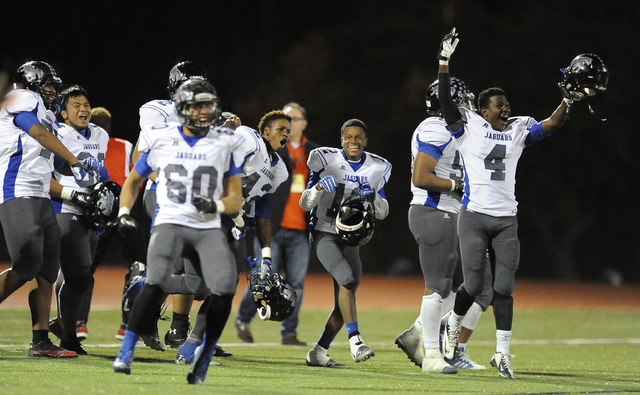 Desert Pines players celebrate their 34-27 upset victory over Faith Lutheran during their Division 1A Southern Region semifinal prep football game at Faith Lutheran High School in Las Vegas Friday ...