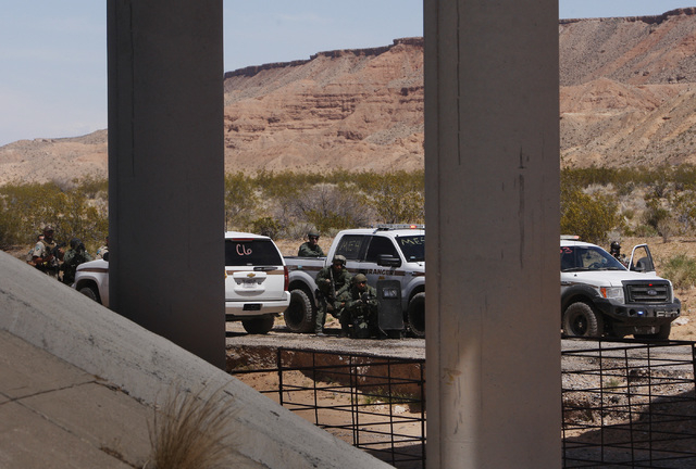 Armed Federal BLM officers stand their ground against the Bundy family and their supporters near their impound corral just outside of Bunkerville on April 12, 2014. (Jason Bean/Las Vegas Review-Jo ...