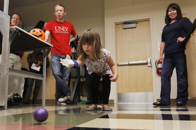 Hailey Dawson uses her new prosthetic hand to roll a ball across the floor Thursday, Oct. 30, 2014 at UNLV. (Sam Morris/Las Vegas Review-Journal)