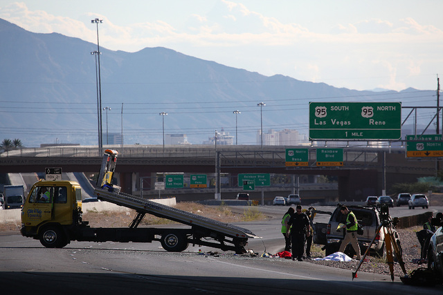 Crews remove a sport utility vehicle that rolled over ejecting one passenger who died on the eastbound Summerlin Parkway near Buffalo Drive in Las Vegas on Sunday, November 2, 2014. (Justin Yurkan ...