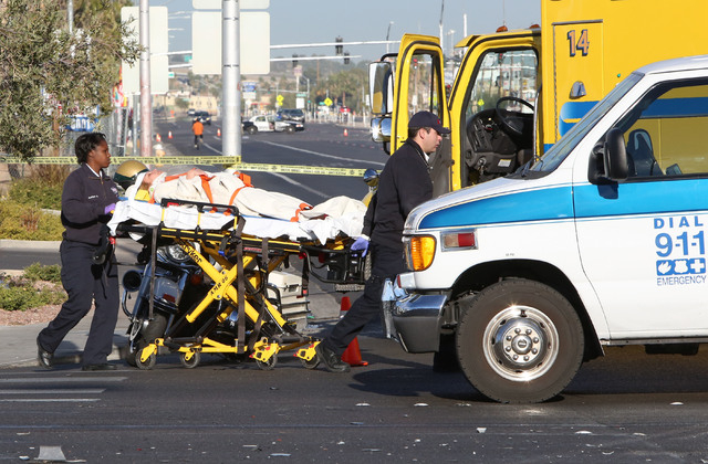 An injured  woman is carried on a stretcher from the accident scene to a waiting ambulance Thursday, Nov. 27, 2014. One person was killed and six others injured in a multi-vehicle crash at Sahara  ...