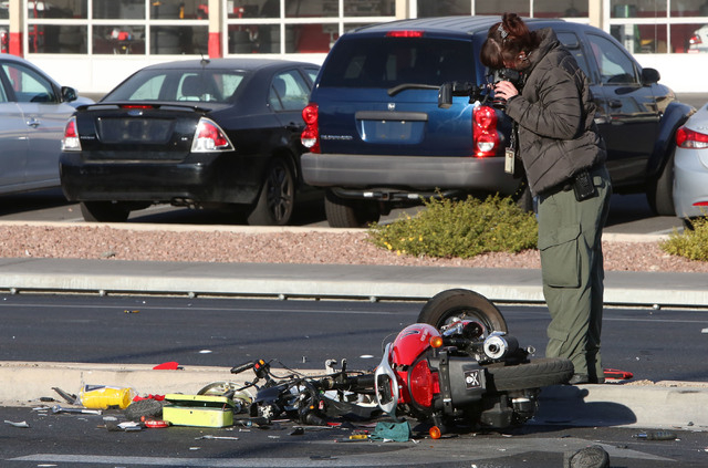 A Las Vegas Police crime scene photographer takes a picture of the accident scene where one person was killed and six others were injured in a multi-vehicle crash at Sahara Avenue and Fremont Stre ...