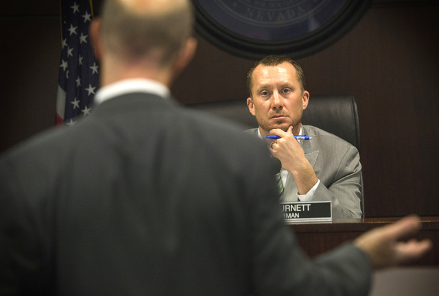 Nevada Gaming Control Board chairman A.G. Burnett,right, listens while Gavin Isaacs, CEO of Scientific Games, speaks during GCB hearing on the company's  buyout of Bally Technologies on Thursday,  ...