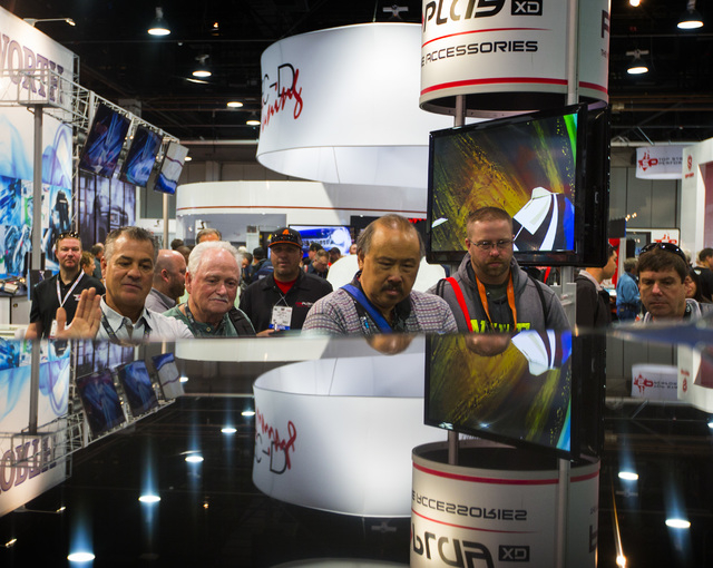 People view the VRX Racing Simulator during the Specialty Equipment Market Association Show at the Las Vegas Convention Center on Tuesday, Nov.4,2014.  Around 60,000 people are estimated to attend ...