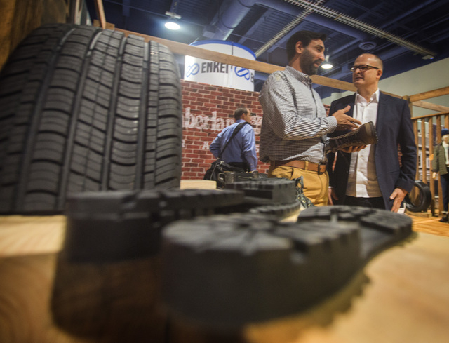 G.S. Sareen, left, CEO of Omni United tire company and Stewart  Whitney, president of Timberline, talk in the Omni United booth during the Specialty Equipment Market Association Show at the Las Ve ...