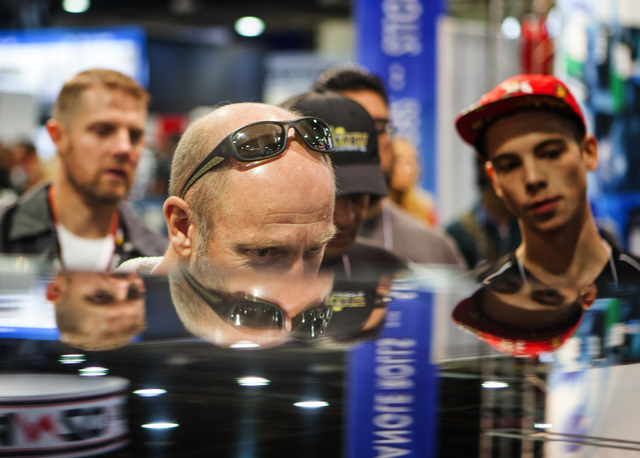Mark Phelan watches his son operate the  VRX Racing Simulator during the Specialty Equipment Market Association Show at the Las Vegas Convention Center on Tuesday, Nov.4,2014.  Around 60,000 peopl ...