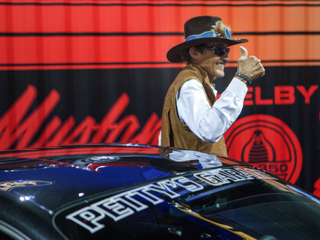 Race car driver Richard Petty stands in front of a 2015 Mustang GT Petty Edition by Petty's Garage in the Ford booth during the Specialty Equipment Market Association Show at the Las Vegas Convent ...