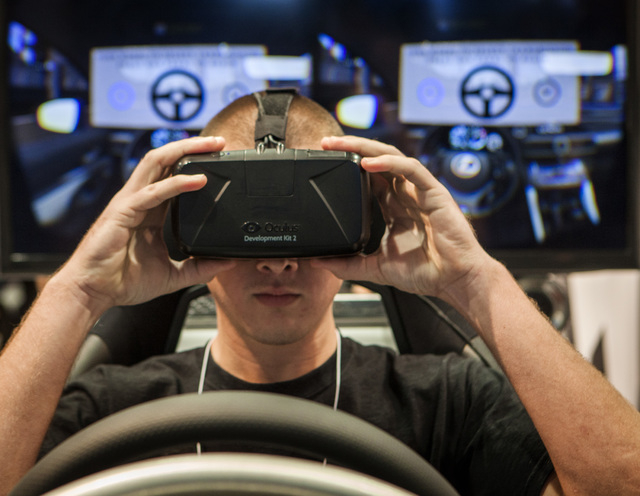 Brandon Duck adjusts goggles while test driving a Lexus RC F sedan simulator in the Lexus booth during the Specialty Equipment Market Association Show at the Las Vegas Convention Center on Tuesday ...