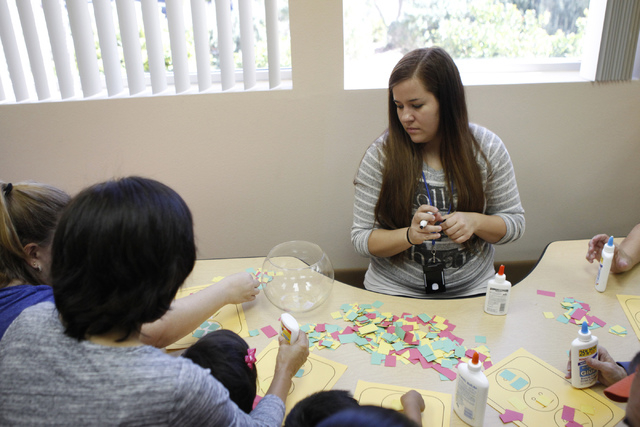 Development specialist Anna Tilaro watches parents and their children create paper crafts during a class at Family to Family Connection, Nov. 5, 2014. (Erik Verduzco/View)