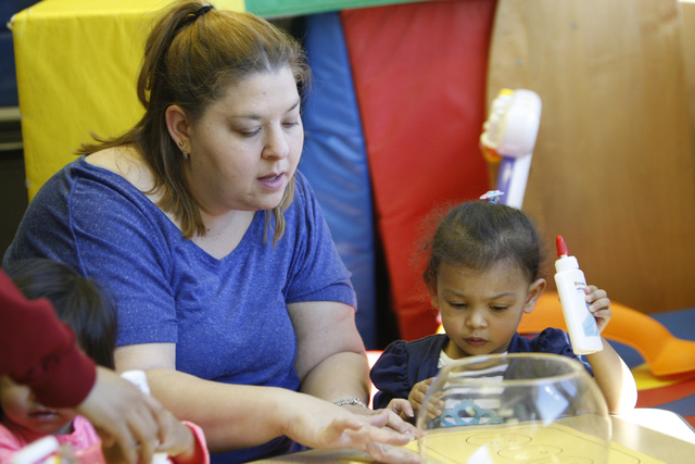 Alana Pelser, left, and her daughter Brianna, 2, create paper crafts during a class at Family to Family Connection, Nov. 5, 2014. (Erik Verduzco/View)