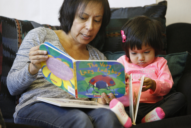 Monica Aldana reads to her daughter Alina, 2, during a class at Family to Family Connection, Nov. 5, 2014. (Erik Verduzco/View)