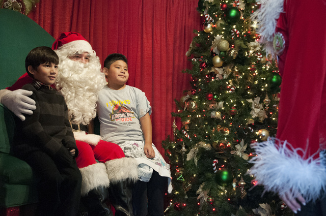 First grade students Nathan Lopez, left, and Diego Maldonado, pose for a photo with Santa Claus during their class visit to Magical Forest at Opportunity Village in Las Vegas in 2013. (Erik Verduz ...