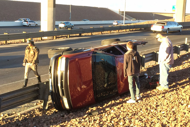 The driver of a Chevy pickup, centers, stands beside his vehicle after it was involved in a two-vehicle crash Thursday morning, Nov.20, 2014, on the exit ramp from the 215 Beltway to Russell Road. ...