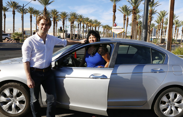 """William Barnes, Uber's western operations manager, left, and Uber driver Emerlita Torres of Las Vegas pose for photo on Thursday, Oct.  23, 2014, near the """"Welcome to Downtown Las Vegas"""" sign on L ..."""