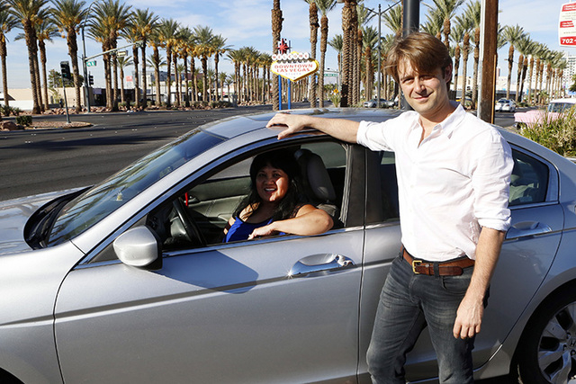 "William Barnes, Uber's western operations manager, right, and Uber driver Emerlita Torres of Las Vegas pose for photo on Thursday, Oct.  23, 2014, near The ""Welcome to Downtown Las Vegas"" sign on  ..."