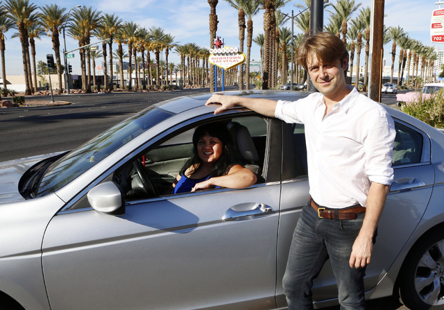 """William Barnes, Uber's western operations manager, right, and Uber driver Emerlita Torres of Las Vegas pose for photo on Thursday, Oct.  23, 2014, near The """"Welcome to Downtown Las Vegas"""" sign on  ..."""