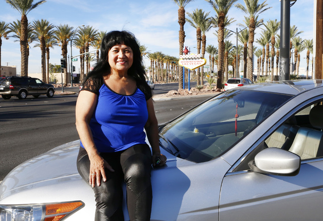 "Uber driver Emerlita Torres of Las Vegas poses for photo on Thursday, Oct.  23, 2014, near The ""Welcome to Downtown Las Vegas"" sign on Las Vegas Boulevard. Uber, the ride-sharing company ..."