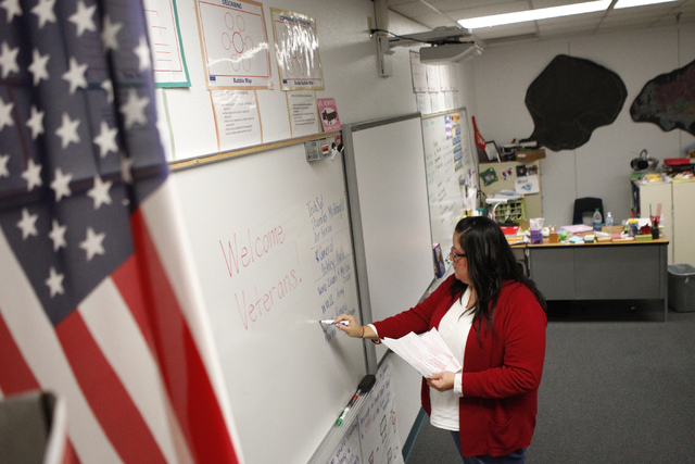 Fifth grade teacher Celia Roberts writes on the board as she gets her classroom ready for military veterans joining her class as guest speakers at at Doris French Elementary School in Las Vegas Fr ...