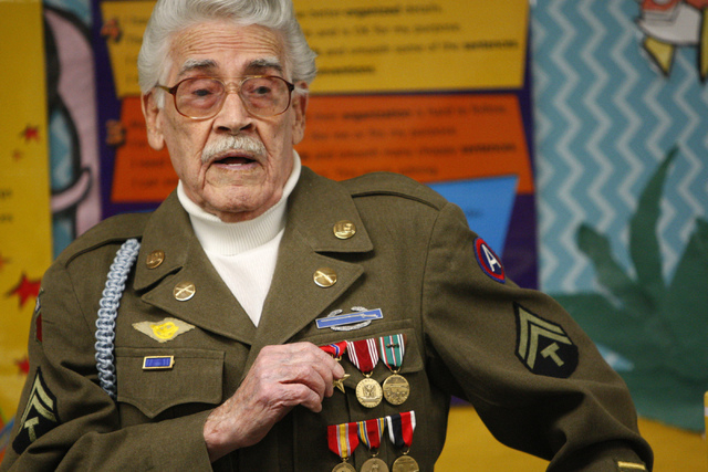 World War II Veteran U.S. Army Tech 5th grade Milton Duran explains his military badges to a fifth grade class at Doris French Elementary School in Las Vegas Friday, Nov. 7, 2014. Veterans from a  ...