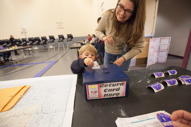 Two-year-old Jackson Ungaro, with his mother, Rachel, returns the activation card for the voting machine at Desert Breeze Community Center in Las Vegas on Tuesday, Nov. 4, 2014. (Chase Stevens/Las ...